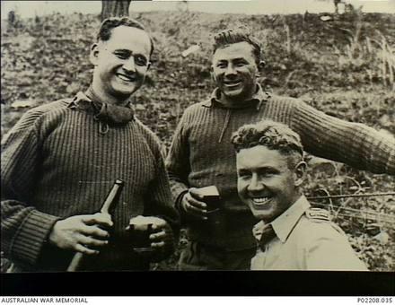 Photograph of 'Three officers from 'A' Company, 3rd Battalion, The Royal Australian Regiment (3RAR), share a bottle of beer in a reserve area. The soldiers are (left to right): Captain Brian Poananga, a New Zealander serving with the battalion; 3/40105 Lieutenant Gilmer John (Gil) Lucas MC; 3/395 Major Jeffrey James (Jim) Shelton MC, the company commander.' Australian War Memorial, P02208.035. Image may be subject to copyright restrictions.