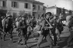 "Kaye, George Frederick, 1914-2004. Soldiers of the Maori Battalion moving into line in the Faenza sector, Italy, during World War II. New Zealand. Department of Internal Affairs. War History Branch :Photographs relating to World War 1914-1918, World War 1939-1945, occupation of Japan, Korean War, and Malayan Emergency. Soldiers of the Maori Battalion moving into line in the Faenza sector, Italy, during World War II. Includes Jack Love (foreground, right), Hapurona Rangi (walking behind Love), and Ned Nathan (beside Love, on his left). Photograph taken by George Kaye on 16 December 1944. Alternative identification of soldiers from the 28 Maori Battalion website (www.28maoribattalion.org.nz), left to right; Monte Robson (39454), Joseph Tai Angell (39288), Colin Fisher (39317), Leslie Pirihi (39688), Edward Nathan (2880) and Joe Hoterene (39332). Many of the men identified either died in Crete in 1941 or were POWs in 1941. Which suggests that either the photo was actually taken at another date/place. Other - Note on back of file print from Library client reads ""Ned Nathan - centre front row - was wounded in Crete, so possibly, this is is not Italy, but Crete..."" Ref: DA-07880. Alexander Turnbull Library, Wellington, New Zealand. /records/23243221"