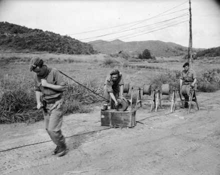 """Men from Charlie troop, Royal NZ Signals Regt, laying telephone cable in Korea. New Zealand. Department of Internal Affairs. War History Branch :Photographs relating to World War 1914-1918, World War 1939-1945, occupation of Japan, Korean War, and Malayan Emergency. Original caption in album PA1-q-315 reads: """"Charlie troop, Royal N.Z. Signal Regt, attached to 1st Commonwealth Signals, laying cable through a dispenser to form a snake of 5 wires. Pulling the 'snake' to the next post is: Sig. A L Philip of Cambridge, N.Z. while Sig, D N [Ngatai ?] of Tauranga, N.Z. guides it through the dispenser. The man in charge of the cable drums is: L/Cpl R. Rigg, of Twickingham, Eng. In one year Div Sigs have laid 10,000 miles of cable. 600 hundred [sic] miles of cable are in use and maintained by Div.Sigs. at present."""" Photograph taken 3 September 1952, by an unidentified New Zealand Army photographer. Ref: K-1338. Alexander Turnbull Library, Wellington, New Zealand. /records/23014910"""
