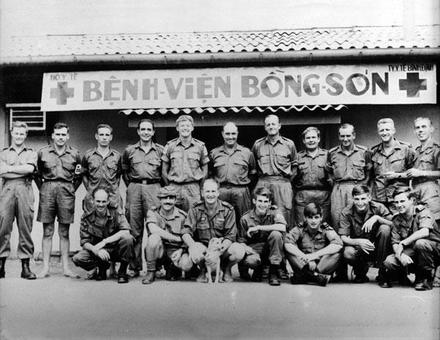 """Members of the 1st New Zealand Services Medical Team outside the hospital at Bong Son, cica January 1970. Back row (left to right): Gordon Watt, Tom Neve, Ian Blakeway, Arthur Norris, 'Blue' Stuart, Alan Earl, Brian McMahon, Owen Snelling, Bob Maitland, Eugene Clements, Gilbert Dampier. Front row (left to right): Len Thompson, Tony Lancaster, Alan White, Dennis Manson, Lindsay Grenfell, Peter Stitt, 'Barney' Bowen. Image provided by Tom Neve, VietnamWar.govt.nz. Image may be subject to copyright restrictions. """