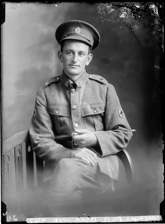 Crown Studios, Auckland. Studio portrait of a soldier. Hat, collar and epaulette badges with Red Cross cloth arm badge denote the Medical Corps, NZEF 22nd Reinforcements. Name from glass plate inscription: Private R.[?] Cashmore. Historical note: Richard Cashmore. Service No. 3/2810. Private. 22nd Reinforcements, New Zealand Medical Corps. (Source: Auckland War Memorial Museum, Cenotaph record). Auckland Libraries Heritage Collections 7003-516. No known copyright restrictions