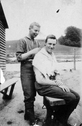 Photograph of 'Ron Wakelin cutting fellow soldier Melve King's hair, outside barracks at Codford Camp, England.' Image coutesy of Wairarapa100. Image may be subject to copyright restrictions.