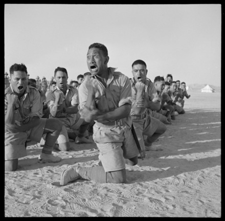 Maori Battalion performing a haka, Egypt. Members of the Maori Battalion who had fought in Greece, performing a haka for the King of Greece at Helwan, Egypt. Photograph taken circa 24 June 1941 by an unidentified official photographer. The four men in the foreground are, left to right; John Manuel, Maaka White, Te Kooti Reihana, and Rangi Henderson. New Zealand. Department of Internal Affairs. War History Branch. Ref: DA-01229-F. Alexander Turnbull Library, Wellington, New Zealand. /records/23061877
