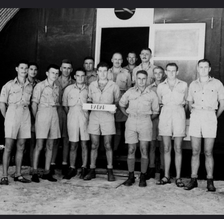 Group photograph of Royal New Zealand Air Force Radar personnel, including William John (Jack) Thomas (third from right, next to the sign). Image kindly provided by Stephanie Williams (May 2020). Image may be subject to copyright restrictions.