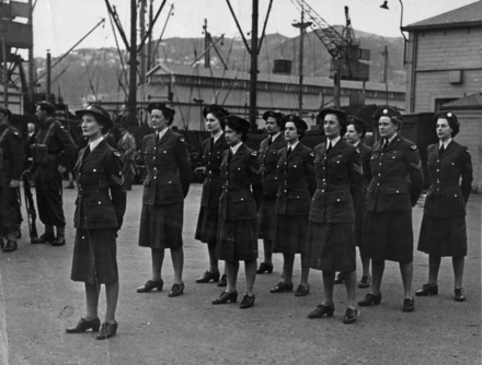 Flight of women on the docks at Wellington, part of the Victory Contingent to London. Front Row L to R: S/Sgt J L Copeland, Sgt J S Milne, Cpl E M Tuapawa, Sgt. C E Reid. Middle Row, WAL E J McGovern, Sgt N C Mercer, Cpl J Beasley, Back Row. Sgt. C F Bryers, Cpl J Mitford-Taylor, Sgt J M Gerrie. Image from the EJ Miller personal album held by the Air Force Museum of New Zealand. Image kindly provided by Air Force Museum of New Zealand CC BY NC 3.0.