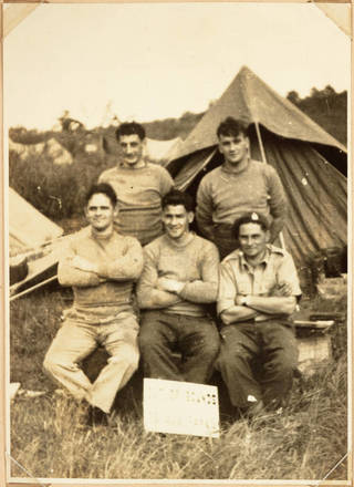 Five New Zealand Support Company soldiers pose for the camera in front of a supply tent at a military training camp, Japan. Left to right back: R. Hill, J.A. McConaghty. Left to right front: J.A. Johansen, D.J. Barnes, S.R.L. Pope. A sign resting on the legs of D. Barnes reads 'Out of Bounds to all ranks.' J.A. Johansen's photograph album of peacekeeping in Japan by the New Zealand Support Company, 22nd Battalion.  Please acknowledge Auckland Libraries Heritage Collections TRS-A01-32-03