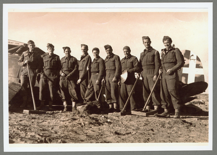 A group of New Zealand Soldiers engaged in clearing abandoned airfields, from Left to Right: J. Corbett (Gore), F. Fenton D.C.M (Auckland), D. Cundy (Wellington), Lieut. R.A. Pickmere (Auckland), M. Vincent (Auckland), R. Hume (Wellington), S. Lewis (Wellington), J. Smith (Wellington), R.S. Evans (Lower Hutt). Image kindly provided by Margaret Pickmere (March 2021).