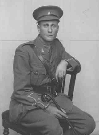 Portrait of Second Lieutenant Varnham seated on a wooden chair holding a swagger stick. No known copyright restrictions
