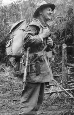 Portrait, Nigel MacKenzie Cotching, with rifle, back pack in countryside - This image may be subject to copyright