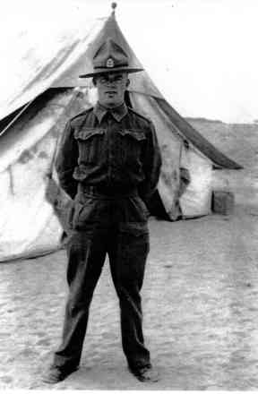 Portrait, Ian McNeur in unform standing outside tent - This image may be subject to copyright