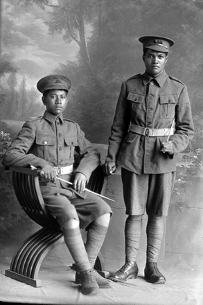 Group portrait of two Privates of the New Zealand Maori Pioneer Battalion, one is Private Richard Abraham, Reg No 16/1397, of the 5th Maori Contingent. (1916). Sir George Grey Special Collections, Auckland Libraries, 31-A2. No known copyright.