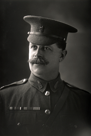 1/4 length portrait of Sergeant Major Eastbury with New Zealand permanent staff, wearing campaign medals (Photographer: Herman Schmidt, 1917). Sir George Grey Special Collections, Auckland Libraries, 31-E3667. No known copyright.