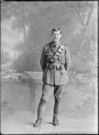 Full length portrait of Trooper William Moody, Reg No 13/410, of the 4th (Waikato) Mounted Rifles, Auckland Mounted Rifles, New Zealand Mounted Rifles, Main Body, smoking a cigar. Killed in action at Gallipoli on the 19th May 1915. (Photographer: Herman Schmidt, 1914). Sir George Grey Special Collections, Auckland Libraries, 31-M825. No known copyright.