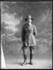 Full length portrait of Colonel James Neil McCarroll, with a moustache, wearing the uniform of the 11th North Auckland Mounted Rifles, campaign medals (Photographer: Herman Schmidt, ). Sir George Grey Special Collections, Auckland Libraries, 31-WP879A. No known copyright.