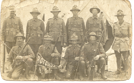 Postcard showing 10 soldiers with small flag reading Rotorua. Those identified are: George Douglas Tayler (12/1515) front row 2nd from left behind the flag and John Albert Harp (12/1425) is back row 5th from left. No Known Copyright.