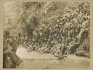 Photograph of No. 2 Platoon, G Company (New Zealand Rifle Brigade), 20th Reinforcements, pausing for a break on the testing Route March from the Featherston Training Camp to Trentham Military Camp (about 40 km) for their pre-embarkation Musketry Course and overseas deployment additional kit issues. Likely date October/November 1916. If you can identify any of the soldiers in this image, please contact Online Cenotaph staff. Image kindly provided by Noel Taylor (August 2018). Image has no known copyright restrictions.